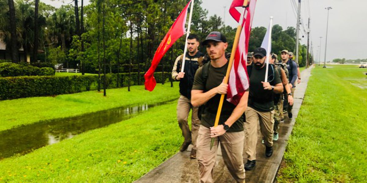 Veterans loaded with gear march to honor fallen troops