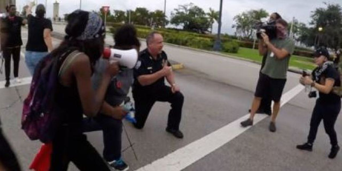 West Palm Beach Police Deputy Chief Rick Morris kneels with protesters