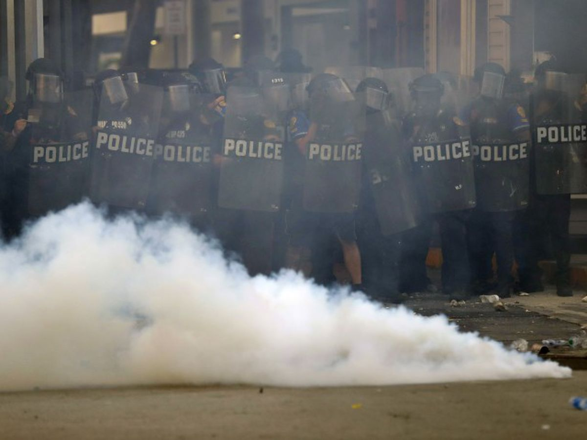 Tear gas fired, police cars burn during protests in downtown Miami