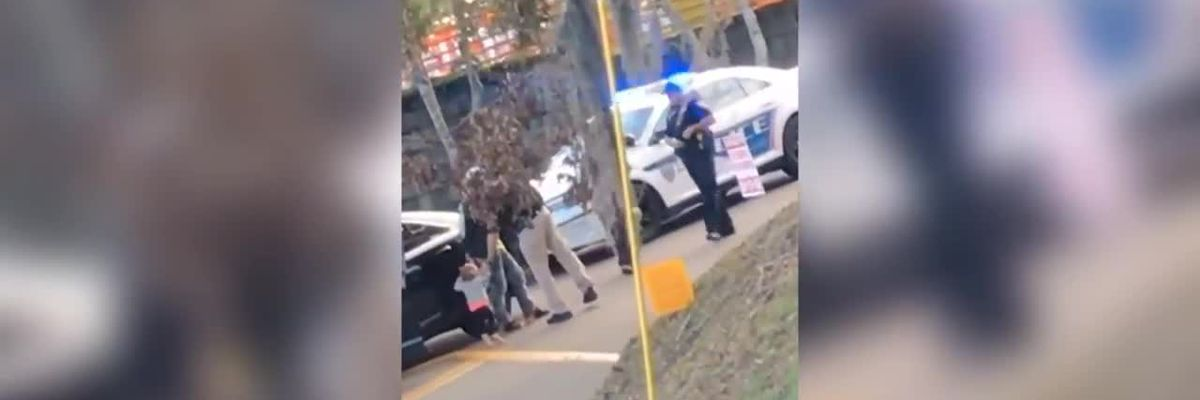 Video shows barefoot toddler with hands up, walking toward armed officers